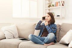 Chica joven en casa que habla en el teléfono móvil Foto de archivo libre de regalías