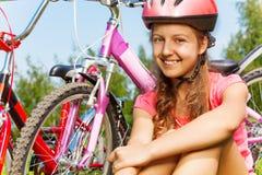 Chica joven en casco rojo con la bici en prado Fotos de archivo libres de regalías