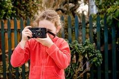 Chica joven en chaqueta roja con la cámara Fotografía de archivo libre de regalías