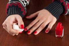 Chica joven en clavos de la pintura del suéter en color rojo y botella en el escritorio de madera Imagen de archivo