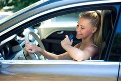 Chica joven en coche con llave del coche Imagen de archivo libre de regalías