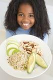 Chica joven en cocina que come la fruta y las tuercas s del arroz Foto de archivo