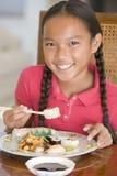 Chica joven en comedor que come el alimento chino Foto de archivo libre de regalías