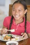 Chica joven en comedor que come el alimento chino Imagen de archivo
