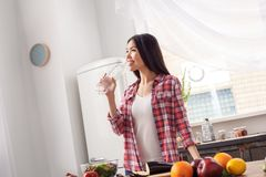 Chica joven en el agua potable permanente de la forma de vida sana de la cocina mientras que corta las verduras alegres imagen de archivo libre de regalías
