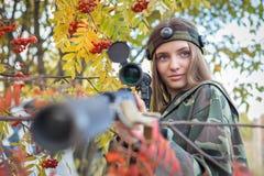 Chica joven en el arbusto de una ceniza de montaña con un rifle de francotirador Foto de archivo