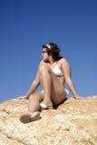 Chica joven en el bikiní que se sienta en las rocas Fotografía de archivo