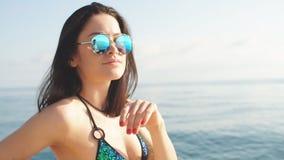 Chica joven en el bikini y las gafas de sol que presentan en un yate en un día de verano soleado almacen de video