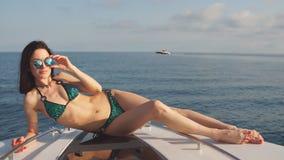 Chica joven en el bikini y las gafas de sol que presentan en un yate en un día de verano soleado almacen de metraje de vídeo