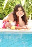 Chica joven en el borde de la piscina Foto de archivo