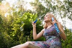 Chica joven en el bosque que juega con las burbujas de jabón Imágenes de archivo libres de regalías