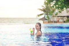 Chica joven en el cóctel de consumición de la piscina imagen de archivo libre de regalías