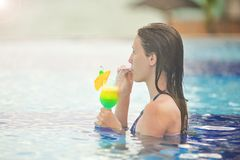 Chica joven en el cóctel de consumición de la piscina Foto de archivo