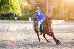 Chica joven en el caballo de bahía que galopa en su curso Imágenes de archivo libres de regalías