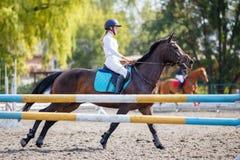 Chica joven en el caballo de bahía que galopa en su curso Imagen de archivo