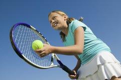 Chica joven en el campo de tenis que se prepara para servir cierre de la opinión de ángulo bajo para arriba imagen de archivo
