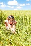 Chica joven en el campo de trigo que sostiene el pequeño perro Imágenes de archivo libres de regalías