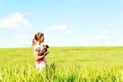 Chica joven en el campo de trigo que sostiene el perro que comtempla la naturaleza Imagen de archivo libre de regalías