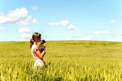 Chica joven en el campo de trigo que sostiene el perro que comtempla la naturaleza Imágenes de archivo libres de regalías