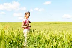 Chica joven en el campo de trigo que sostiene su pequeño perro Foto de archivo libre de regalías