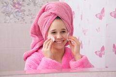 Chica joven en el cuarto de baño que limpia su cara con los cojines de algodón Fotos de archivo