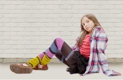 Chica joven en el estilo del inconformista, sentándose en el piso Imagenes de archivo