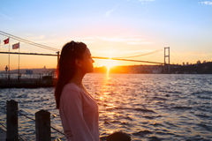 Chica joven en el fondo del puente y de la puesta del sol de Bosphorus Fotografía de archivo