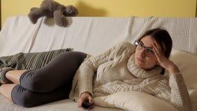 Chica joven en el invierno que iguala en casa en un suéter blanco en el sofá con los vidrios que ve la TV tarde Casa comodidad almacen de metraje de vídeo