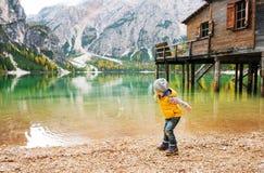 Chica joven en el lago Bries en las piedras que saltan del otoño Foto de archivo