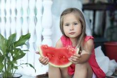 Chica joven en el pórtico de la casa que come la sandía dulce Foto de archivo