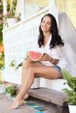 Chica joven en el pórtico de la casa que come la sandía dulce Fotos de archivo
