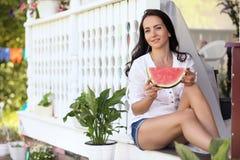 Chica joven en el pórtico de la casa que come la sandía dulce Imagenes de archivo