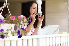 Chica joven en el pórtico de la casa que come la sandía dulce Imagen de archivo libre de regalías