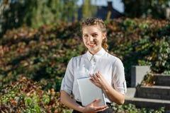 Chica joven en el parque con una tableta a disposición imagen de archivo