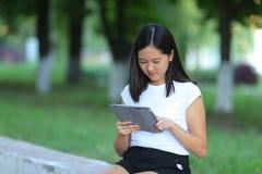Chica joven en el parque que aprende con la tableta Fotos de archivo