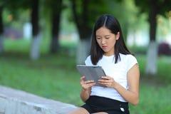 Chica joven en el parque que aprende con la tableta Imágenes de archivo libres de regalías