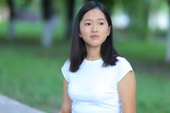 Chica joven en el parque que aprende con la tableta Foto de archivo libre de regalías