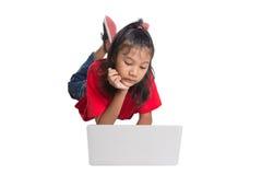 Chica joven en el piso con el ordenador portátil VI Fotos de archivo