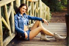 Chica joven en el puente de madera Foto de archivo libre de regalías