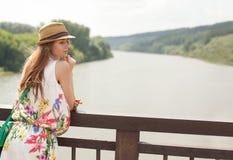 Chica joven en el puente en el vestido blanco con las flores y el sombrero que presentan en la puesta del sol en la orilla del rí Fotos de archivo