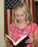 Chica joven en el readig de la escuela delante de la clase foto de archivo libre de regalías