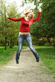Chica joven en el salto rojo de la camisa al aire libre Fotografía de archivo