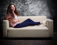 Chica joven en el sofá Fotos de archivo