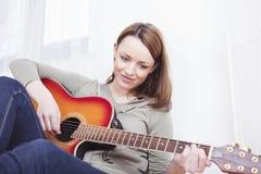 Chica joven en el sofá que toca la guitarra Imagenes de archivo