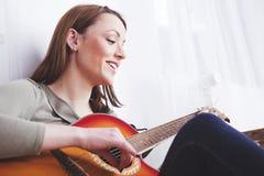 Chica joven en el sofá que toca la guitarra Fotografía de archivo libre de regalías
