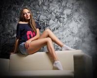 Chica joven en el sofá Foto de archivo libre de regalías