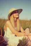 Chica joven en el sombrero de paja que se sienta en campo Imagen de archivo