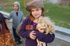 Chica joven en el sombrero que sostiene la muñeca Fotos de archivo