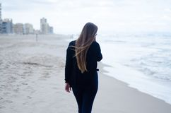 Chica joven en el suyo detrás, caminando en la playa en un día nublado fotos de archivo libres de regalías
