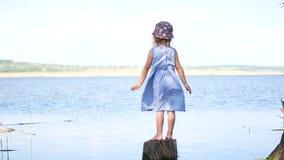 Chica joven en el vestido que se coloca con los brazos abiertos en la orilla del lago almacen de metraje de vídeo